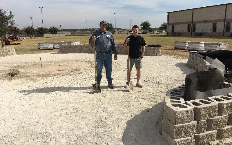 Greg Lewis, owner of GAL Horticultural Services, and Texas FFA Ford Leadership Scholar, Hunter Hackley, inspect construction of the JHS Memorial Courtyard.