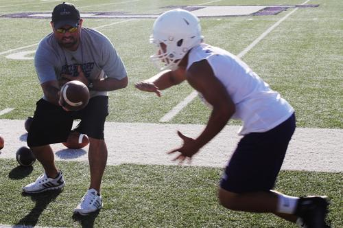 Jacksboro Coach Brian Hodnett hands off to a player during a drill Monday as part of a drill. Scrimmages begin Saturday with the intra-squad scrimmage,