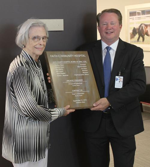 FCH Board Member Edwina Swan, left, and FCH Administrator/CEO Frank Beaman hang the dedication plaque in the lobby of the hospital during Saturday's dedication.