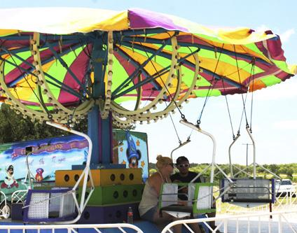 Carnival workers take a break from the heat Wednesday afternoon when they were preparing to open at Twin Lakes Thursday. The carnival is a new addition to the TNT Fest event which is set for Saturday.