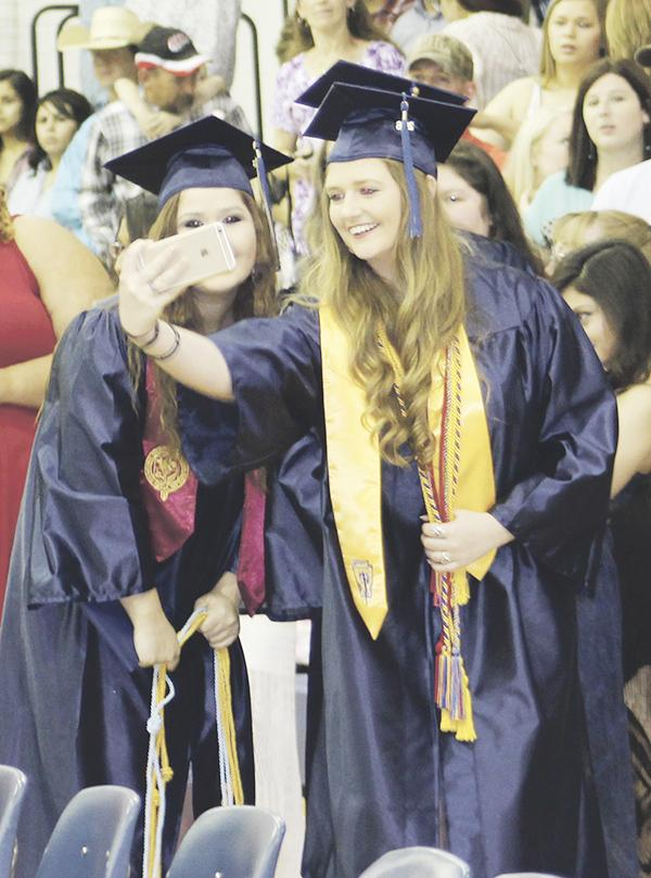 Two Perrin grads pause for a selfie during the recessional following the commencement ceremony Friday, May 27.