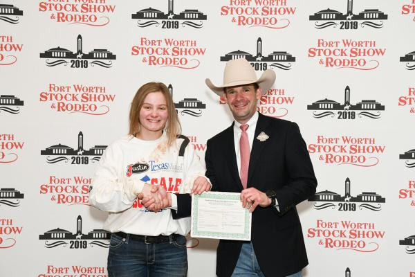 Elizabeth Hines, Jack County 4-H member, caught a calf during Fort Worth Stock Show and Rodeo's Calf Scramble, earning a $500 purchase certificate presented by Paxton Motheral, calf scramble committee member.