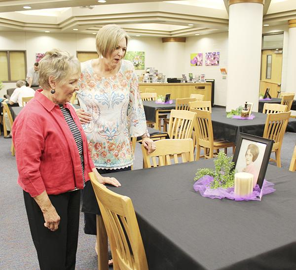Ann Kaker, former second grade teacher, and Diana White admire a photo of White from high school during the retirement reception Monday at the Jacksboro High School library.  Photo / Cherry Rushin
