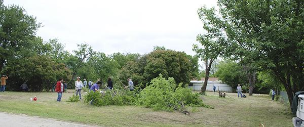 Volunteers clean up the lots at the southwest corner of South 3rd and Pine streets Saturday. Approximately 25 to 30 people came out to trim trees, clear brush, mow and more for the site of Jacksboro's soon-to-be newest park. Courtesy / Terry McDaniel