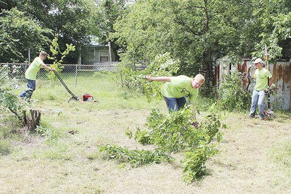 Student volunteers mow, trim trees and remove brush at a property on South 9th Street Saturday as part of Operation Restoration. Organizers from the Jacksboro FFA with participants from several student groups and more, hope to make the community service project an annual event.