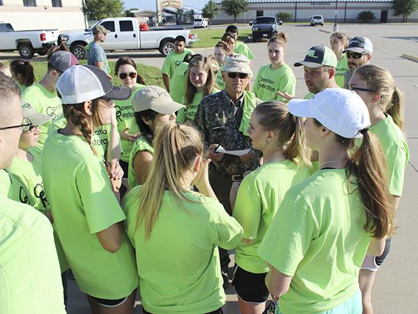 Volunteers gather at the Jacksboro High School ag building to split up in groups, gather tools and learn which locations they will be tackling.