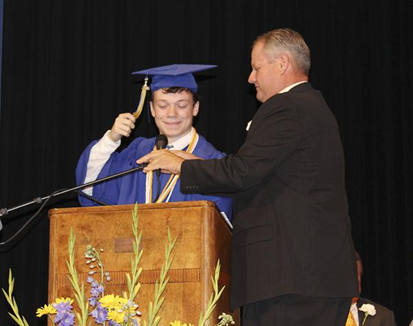 Bryson Superintendent David Stout adjusts the microphone for Salutatorian Jacob Jonas before he gives his address.