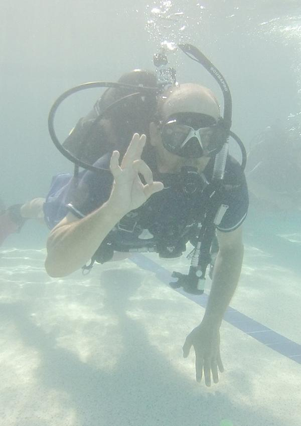 John Moffit gives an OK sign during dive training last weekend at the city pool. Moffit and four other firefighters are training for diving certification.