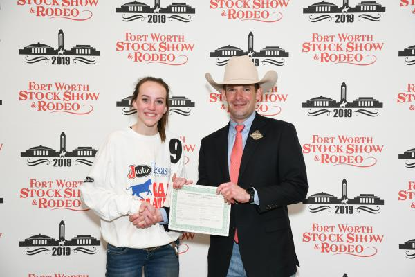 Abigail Mangum, Jack County 4-H member, caught a calf during Fort Worth Stock Show and Rodeo's Calf Scramble, earning a $500 purchase certificate presented by Paxton Motheral, calf scramble committee member.
