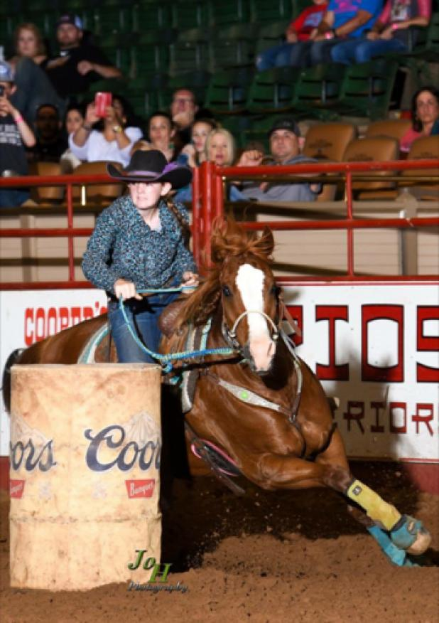 Mika Shackelford makes her way around a barrel during a rodeo competition.