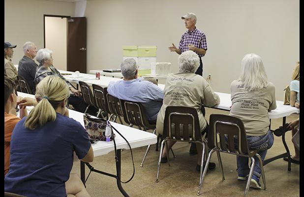 Kent Olsen, a professional beekeeper, discusses beekeeping for a group at the Jack County Fair Barn in October. Olsen will return to Jacksboro to share his expertise June 2 during the museum's Pioneer Day.