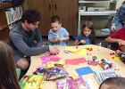 Emerson Cleghorn, center, and Brynlee Cleghorn, right, create alphabet collages during craft time led by Trey Berry, left.