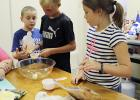 Jonathan Moser, center, measures ingrediants for sweet and salty cereal bars during the Jack County AgriLife Extension cooking camp Tuesday as Caiden Martin and Rebecca Bright look on.
